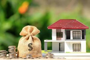 Bolsa de arpillera con símbolo de dólar junto a pilas de monedas y casa en miniatura foto