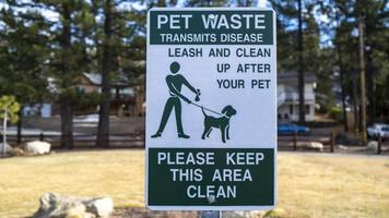 A leash and clean after your pet sign in the park