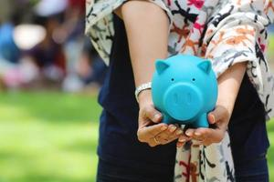 Outstretched arms and hands holding blue piggy bank with outdoor background