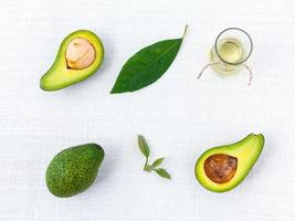 Avocados and oil on white background