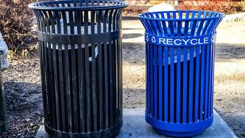 A black and blue metal recycle bin in the park