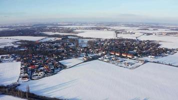 drone orbitando uma vila e campos brancos como a neve em 4k video