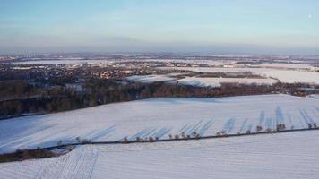 Vista aérea de una carretera con árboles y largas sombras en campo blanco nevado en 4k