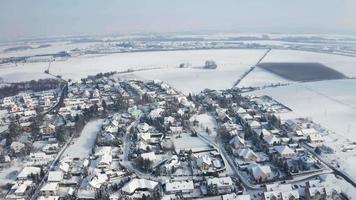 Aerial view of a frozen snowy village on a sunny winter day in 4K