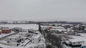 Drone ascending above cloud and white snowy houses in village with houses in 4K