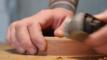 Holzarbeiter planiert ein Mahagoni-Teetablett mit Spänen. enthält asmr sound video