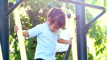 Little girl in T-shirt stands on outdoor fitness equipment on sunshine day.