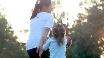 Two little girls and mother exercising together in a park.