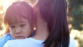 madre consolando a su niña llorando en un parque al aire libre.