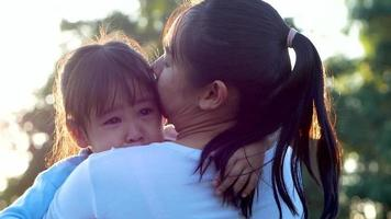 Mother comforting her crying little girl in an outdoor park.