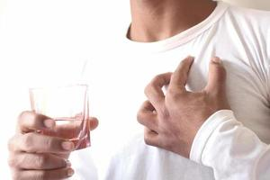 Hombre sujetando un vaso de agua y sufriendo dolor de corazón foto