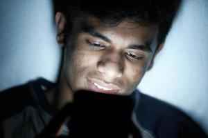 Young man sitting on bed using smartphone at night