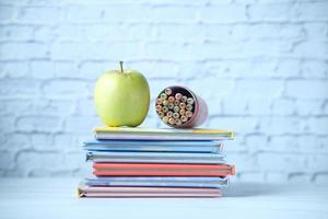 Colorful books, an apple and colored pencil on table