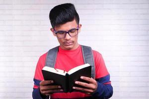 Hombre sosteniendo un libro sobre fondo de ladrillo foto