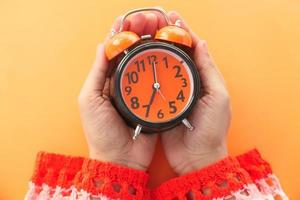 Woman hand holding an alarm clock on orange background