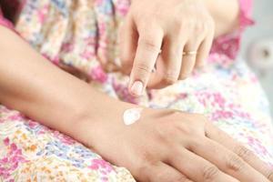 Mujer aplicando crema de belleza sobre la piel en casa, vista superior foto