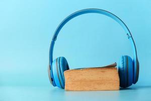 Auriculares y bloc de notas sobre fondo azul. foto