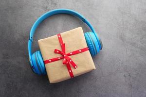 Gift box and headphones on black background photo