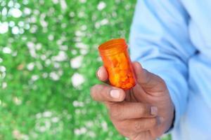 Persona sosteniendo un contenedor de pastillas contra el fondo verde foto