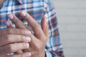 hombre que sufre dolor en primer plano del dedo foto