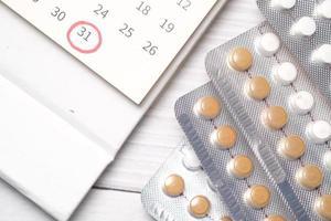 Píldoras anticonceptivas, un calendario y un bloc de notas sobre una mesa foto