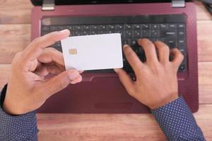 Hombre sosteniendo una tarjeta de crédito y usando una computadora portátil para comprar en línea foto