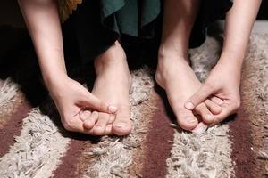 Mujer joven masajeando los pies y sufriendo dolor foto