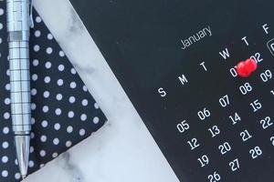 Deadline concept with red push pin on calendar date photo