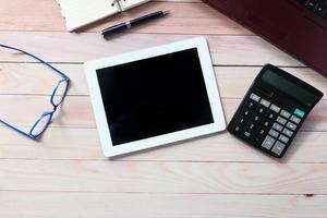 Flat composition of digital tablet and office stationery on wood background photo