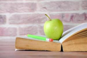 Green apple on a open book on table