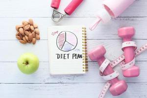Plan de dieta con manzana y mancuernas sobre fondo de madera blanca foto