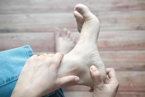 Mujer masajea los pies en el lugar de la lesión foto