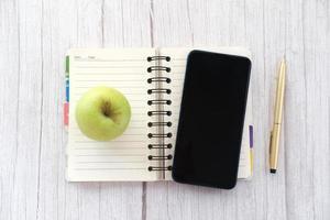 Vista superior del teléfono inteligente, Apple y Bloc de notas en la mesa foto