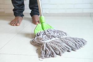 Barefoot person cleaning tile floor with mop