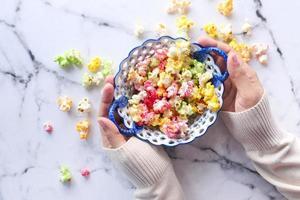 Vista superior de las manos de la mujer sosteniendo un tazón de palomitas de maíz de colores foto