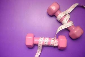 Concepto de fitness con mancuernas y cinta métrica sobre fondo púrpura foto