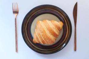Croissant recién horneado en placa con espacio de copia