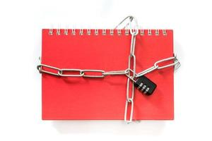 Red notebook chained with combination lock on white background