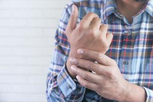 Hombre sujetando su muñeca y sufriendo dolor en la mano con espacio de copia foto