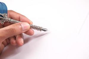 La mano del hombre escribiendo con pluma estilográfica sobre fondo blanco.