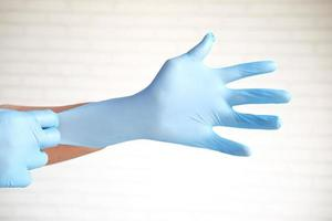 Doctor wears medical gloves, close-up photo