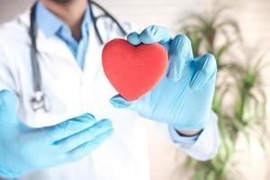 La mano del médico en guantes de látex sosteniendo un corazón rojo de cerca