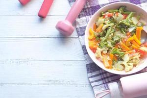 concepto de fitness con mancuernas, verduras frescas y cinta métrica en rosa foto