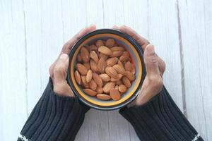 Close-up of senior woman hand holding a bowl on almonds