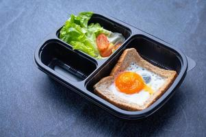Sectioned plastic food container with salad, toast, and fried egg