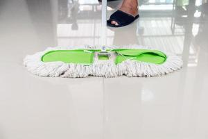 Person with dust mop sweeping tile floor