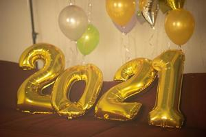 Gold 2021 balloons on red table with colorful balloons in background