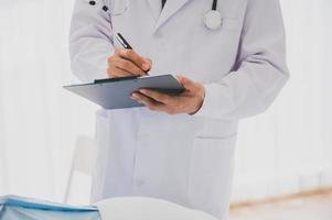 Male doctor with lab coat and stethoscope holding clipboard and pen photo