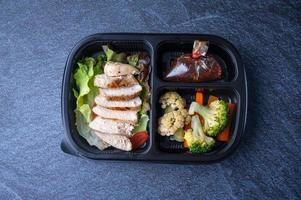 Sectioned plastic food container with sliced chicken salad, broccoli, carrots, and cabbage