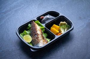 Sectioned plastic food container with salad, grilled fish, and vegetables